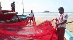 Local fishermen sorting nets on beach after long night working. Stock Footage