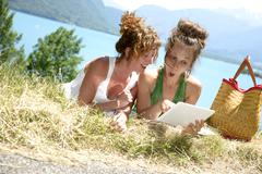 Two pretty girls on the grass with a digital tablet Stock Photos