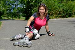 young woman fell on skates - stock photo