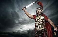 legionary soldier over stormy sky - stock photo