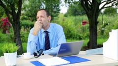Businessman eating apple, having a break by the desk in the garden HD Stock Footage