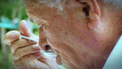 Old  wrinkled man eating  soup outdoor: 4k close up footage Stock Footage