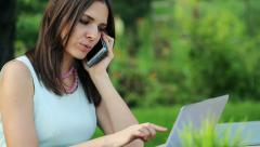 Businesswoman with cellphone and laptop working in the garden HD Stock Footage