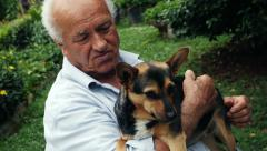 old retired man hugging little dog: 4k footage - stock footage
