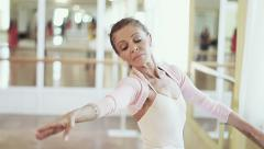 Elderly ballerina holds on to barre and practices ballet moves Stock Footage
