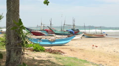 View of wooden fishing boats on beach in Weligama, Sri Lanka. Stock Footage