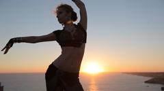 Graceful girl dancing oriental dance at sunset Stock Footage