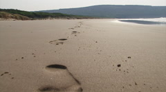 Following Footprints in the Sand Stock Footage
