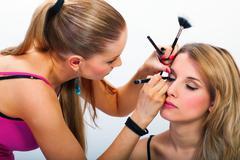 make-up artist applying mascara - stock photo