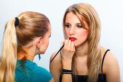 make-up artist applying lipstick on model's lips - stock photo