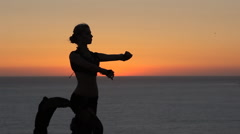 Pretty young girl dancing oriental dance at sunset Stock Footage