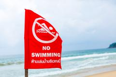 No swimming danger sign at the beach Stock Photos