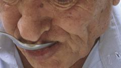 Aged man eating soup: sad, poor, destitute, wrinkled Stock Footage