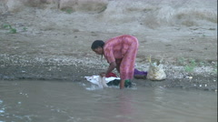African woman washing cloths in river Wide Shot - stock footage