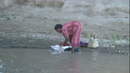 Stock Video Footage of African woman washing cloths in river Wide Shot