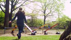 A Mother Runs Over To Her Son And Helps Him On The Seesaw Stock Footage