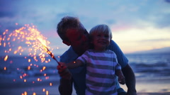 Father and son lighting sparklers on the beach Stock Footage