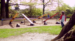 Little Boy Runs To Seesaw In Park, Lifts Up And Lets It Drop Stock Footage
