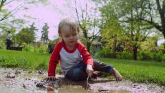 Little Boy Throws Mud In Puddle, And Stirs Puddle With Stick Stock Footage