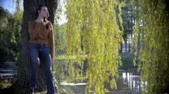 Beautiful model leans on tree and walks toward lake - stock footage