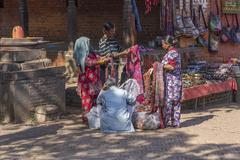 two ladies unidentified negotiate the price of clothing - stock photo