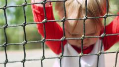 Little Boy Leans Up Against Tennis Net On An Empty Court Stock Footage