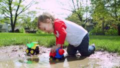 Little Boy Splashes In Mud Puddle And Plays With Toy Trucks Stock Footage