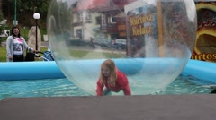 Girl play in bloat water ball floating at water - water amusement Stock Footage
