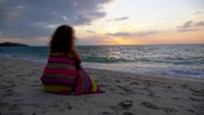 Stock Video Footage of Worried Sad Girl Sitting on the Beach at Sunset. Slow Motion.