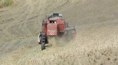 Wheat harvest with modern combine harvester, in difficult  countryside Stock Footage