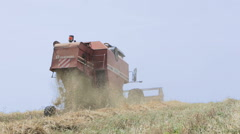 Wheat harvest with modern combine harvester in a wavy field; agriculture Stock Footage