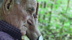 Troubled elderly sitting alone and thinking: sad, upset, depressed.  Stock Footage