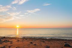 Ocean shore at sunrise Stock Photos