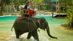 Luang prabang, laos - circa dec 2013: tourists ride on elephants. such entert Stock Footage
