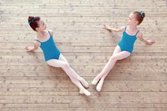 Two little ballerinas posing on wooden floor Stock Photos