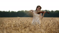 Girl violinist playing the violin in wheat field. Movement medium shot. Stock Footage
