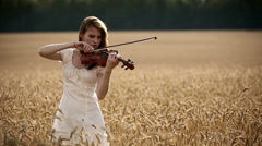 Girl violinist playing the violin in wheat field. Medium shot. Stock Footage