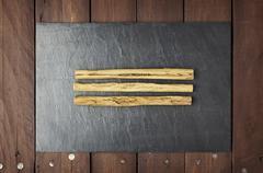 cinnamon sticks on slate plate - stock photo