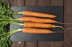 real carrots on slate plate - stock photo