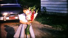 1108 - a young girl holds a large bouquet of flowers - vintage film home movie Stock Footage
