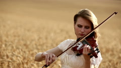 Girl violinist playing the violin in wheat field. Closeup. Stock Footage