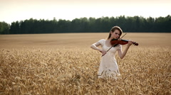 Stock Video Footage of Girl violinist playing the violin in wheat field. Medium shot.
