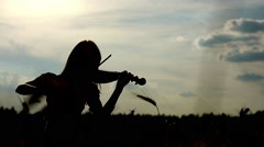 Silhouette girl violinist playing the violin in wheat field sky background Stock Footage