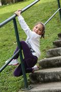 happy little girl climbing railing - stock photo