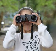 Girl looking through binoculars Stock Photos