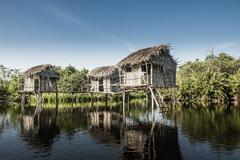 Thatch houses built over rural lake Stock Photos