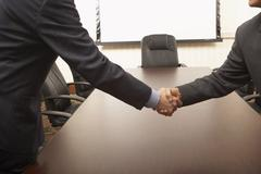Businessmen shaking hands over conference table Stock Photos