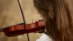 Girl violinist playing the violin in wheat field. Close up. - stock footage