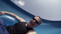 Slow motion POV of man sliding down a water slide Stock Footage