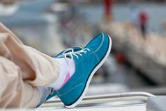 A pair of human legs in pants and bright blue topsiders Stock Photos